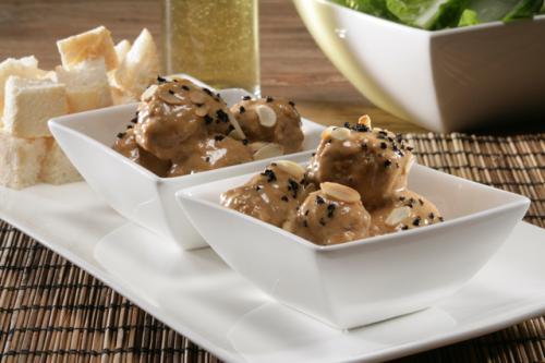 Albondigas met gehakte amandelen en zwarte olijven in truffelsaus
