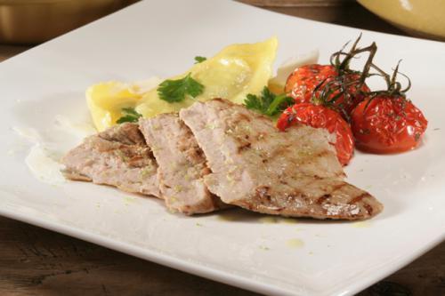 Cotolette alla griglia con limone, pomodori arrosto con olio d'oliva, parmigiano grattugiato e ravioli agli spinaci