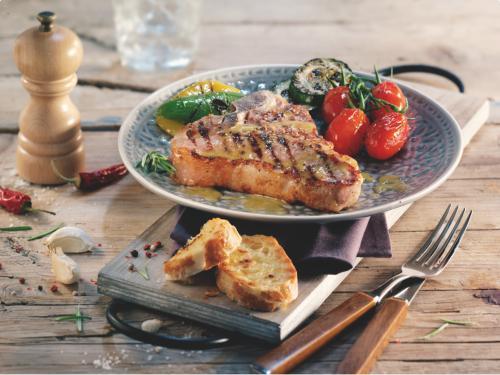Sappige T-bone steaks met sinaasappelsaus, knoflookbrood en gegrilde groenten